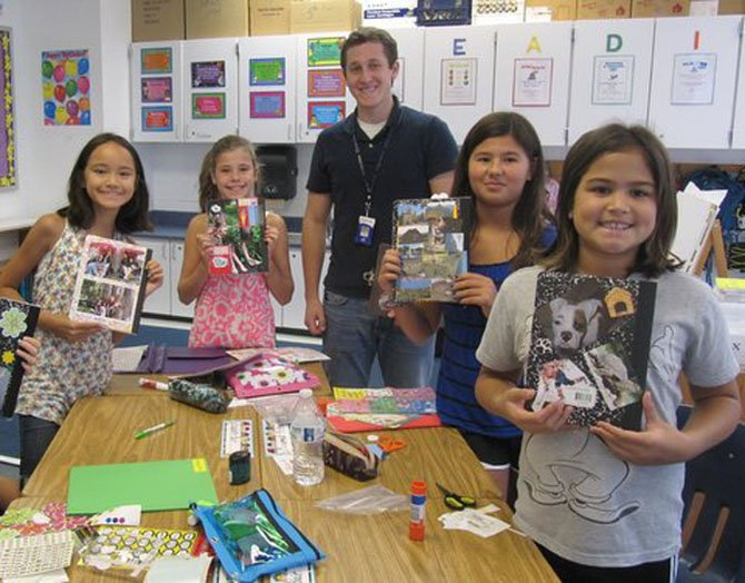 Churchill Road fourth graders Jane Gerrard, Anna Krause-Steinrauf, Isabella Hendricks and Martina Wetten display the creative writing notebooks that they created in Louis Depa's language arts class.