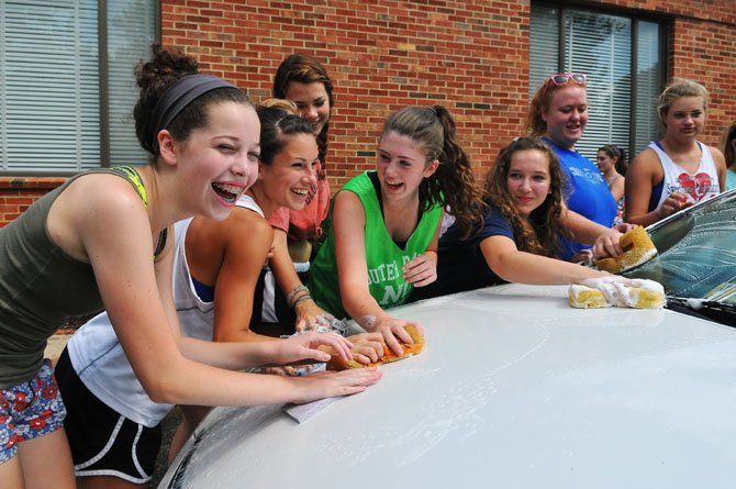The dance team gets down to work with the sponges soaping up a waiting car.