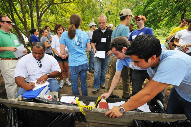 Volunteers sign waiver forms and pick-up gardening gloves at Bon-Air Park.