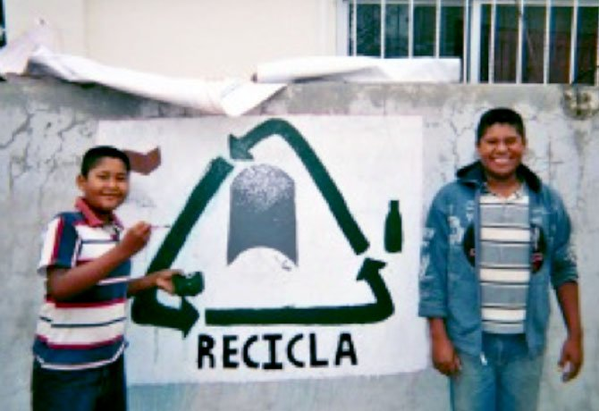 Justin Seara's host brothers (from left) Cristian, 14, and Ivan, 15, standing next to a freshly painted recycling mural.