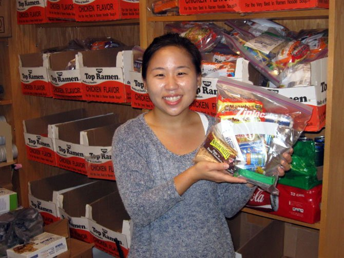 Centreville Elementary counselor Esther Kang holds up a sample of the food bags that children will receive.