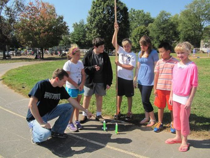 Churchill Road sixth graders Ginevra Augustini, Jake Bickel, Mitchell Farah, Chrissy Frantz (science teacher), Eric Sun and Molly Ferris listen while science teacher Steven Nicklas explains how to prepare alka-seltzer fueled rockets for launch.