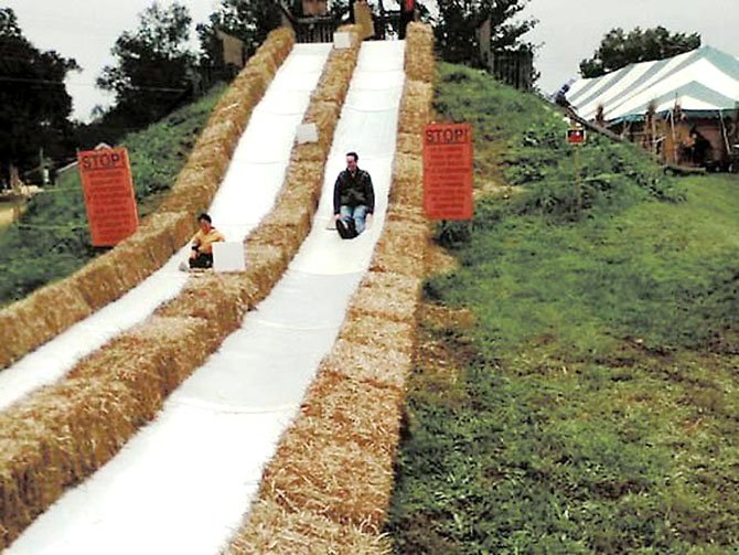Richard Graves and son Evan slide down one of the carpet slides at the Burke Nursery Pumpkin Playground last year.