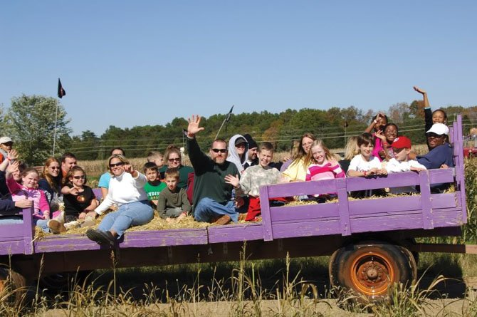 Visitors to Cox Farms enjoy a hayride. In the background are some of the giant slides.