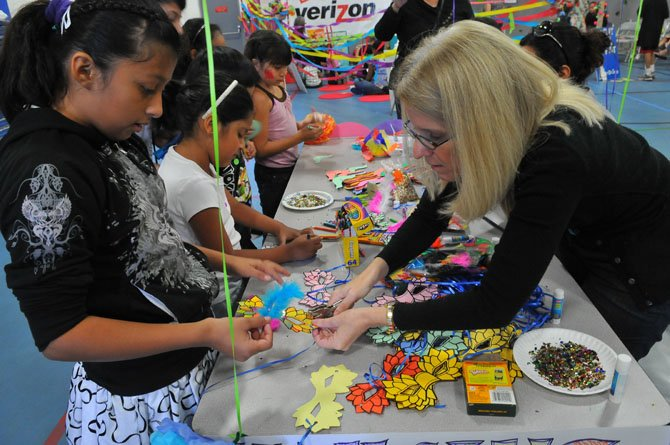 Carol Green helps youngsters sort through all of the decorations that might be put on a mask.
