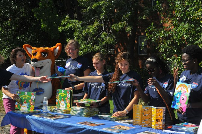 Volunteers fill a table with books for children passing by.
