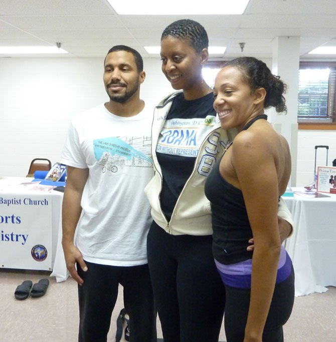 Nigel Greaves, Faith Bynoe and Daemon Jones pose for a photo following a yoga demonstration at the Alfred Street Baptist Church Community Health Fair.