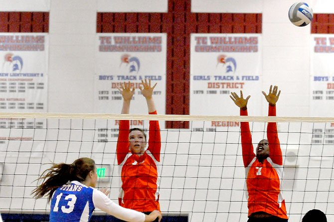 West Springfield middle blockers Destini Davis (7) and Savannah Schutzmeister leap to block against T.C. Williams' Kate Whitmire on Oct. 2.