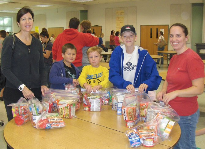 From left: Elisa Newell; Will Eging, 8; Jonathan Newell, 7; Will Newell, a Stone Middle seventh-grader; and Lisa Schilling are at a table with some of the bags they filled.
