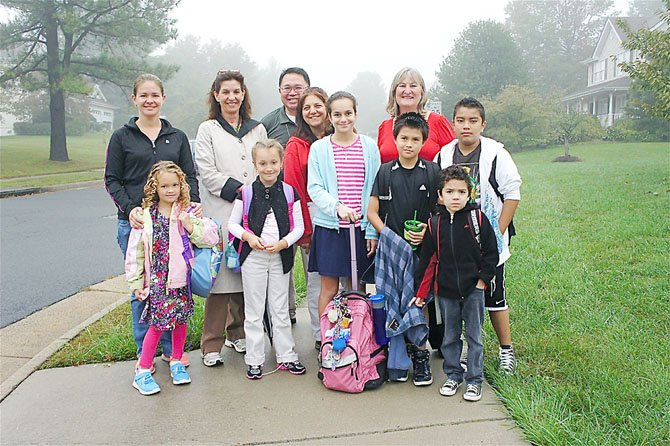 First gathering point: Dranesville Elementary students Mia, Lexi, Rose, Willy, Michael and Jeffrey (up front, right) are ready to take part in International Walk to School Day. They were accompanied by a few parents, and by school Principal Kathryn Manoatl, prepared for the weather with her raincoat, and dressed in red school, Registrar Chris Toye.