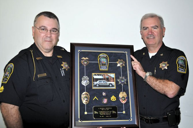 (From left) MPO Randy Burchfield shown with his presentation shadowbox and Colonel Robert A. Carlisle, chief of police.