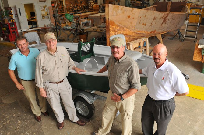 Alexandria Seaport Foundation executive director Kent Barnekov and foundation board member Rex Wagner turned over a repaired fly fishing boat to Healing Waters National Capital Regional Coordinator George Gaines and Roger Carlson on Oct. 4.