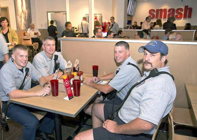 City of Fairfax Fire Department Captain Jeremy Speakes, right, tries a Smashburger with other fire officials.