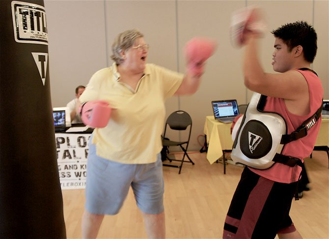 Karyl Moesel of Vienna looks like a pro as she spars with trainer AJ Smiley from Title Boxing Club in the City of Fairfax. Moesel says she was looking for something a little more active and interesting than the traditional offerings for the Non-Youth groups.