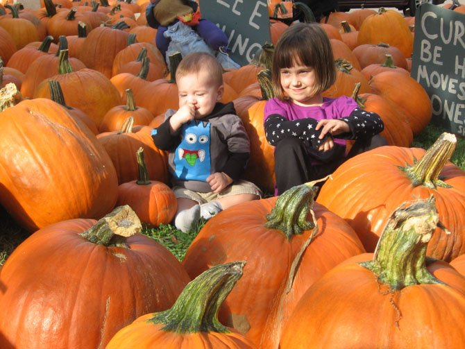 Carter Moorman and Claire Trombley sit among the pumpkins.