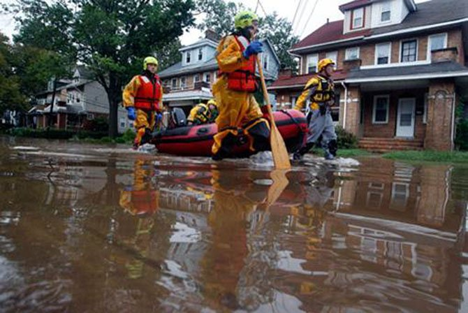 Firefighters pull rescue boats for Huntington residents whose homes were flooded during Tropical Storm Lee.
