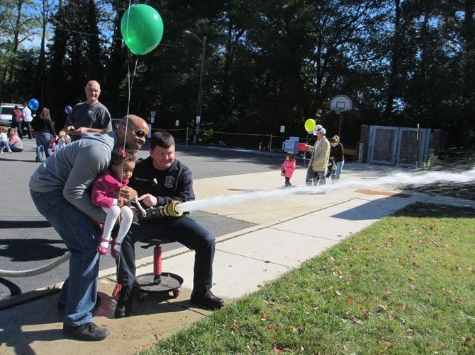 Chloe Edmondson, with a bit of help from her father and a firefighter, aims a powerful spray of water at a target.