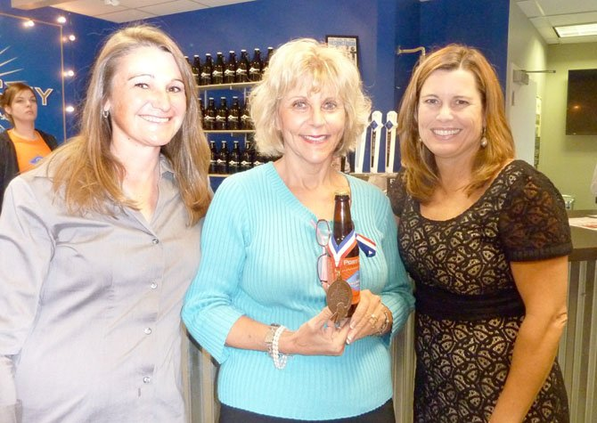 Port City Brewery's Jen Chace, Janet Barnett and Cathy Puskar at the Senior Services of Alexandria's Oct. 16 Oktoberfest to support Meals On Wheels. Barnett is holding Port City's bronze medal-winning Monumental IPA craft beer.