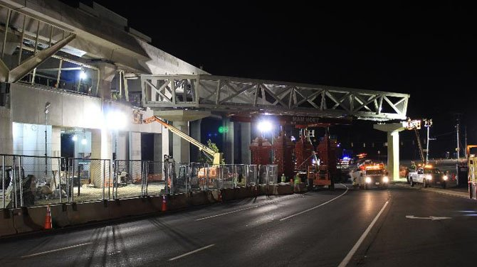 The first section of the pedestrian bridge across Route 123 into the McLean Station, aka Tysons East Metrorail Station, is put into place. At left, workers inside the station itself watch as crews connect the bridge section to the station.
