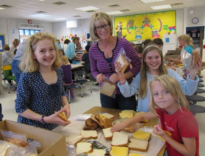 Churchill Road sixth graders Rachel Keiser and April Holmes make sandwiches with the assistance of Caroline Soutter and first grader Tenley Overdeck.