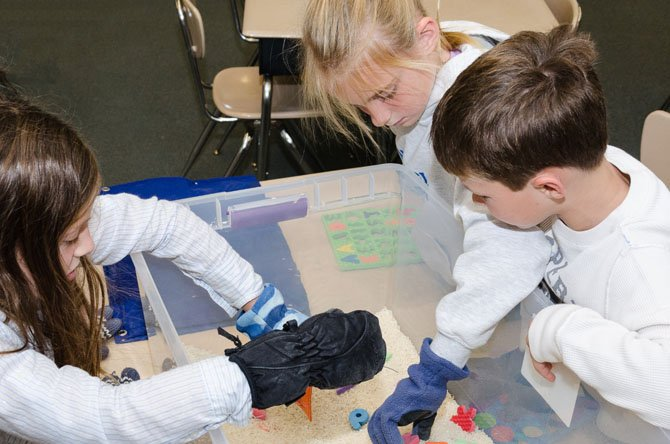 Students from Wayside Elementary School in Potomac wear mittens while trying to pick up small objects in a container. The activity, which is part of the school's Special Needs Awareness Week, is designed to simulate sensory deprivation.