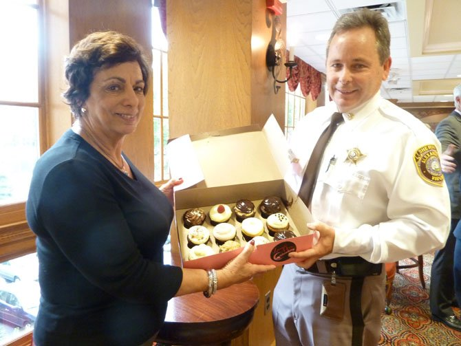 Meals on Wheels program coordinator Dolores Viehman presents Chief Deputy Tim Gleeson with cupcakes from Lavender Moon in appreciation for the volunteer services provided by the Sheriff's Department.