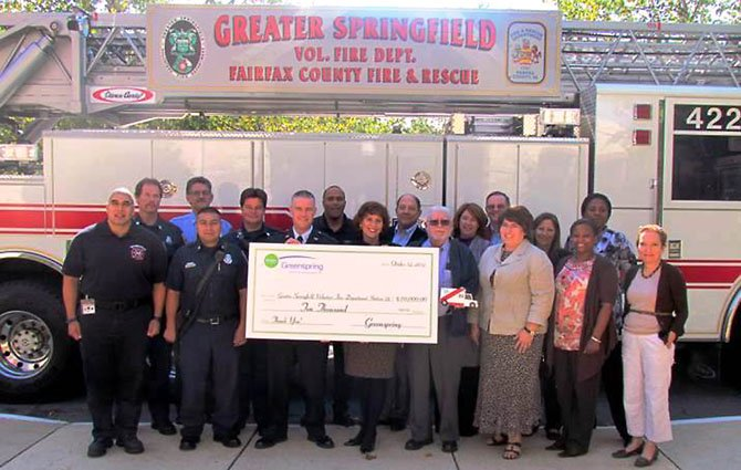 (From left) Station 22 Firefighters Sergio Nava, Mark Huehn, Rick Machado, Luis Mata, Bobby Bookwalter, Fire Chief Blake Payne; Greenspring staff members Ken Roland, Executive Director Robin Gliboff, Berwick Drews, resident Bill Campbell, Kimberly Nelson, resident Roy O'Connor, Lynn Keefe, Holly Borrero, Tamika Mitchell, Karen Boyce, Lee Long. Resident Bill Campbell, holding a small medic truck, made the truck at Greenspring's woodshop and presented it to the Station 22 Firefighters.