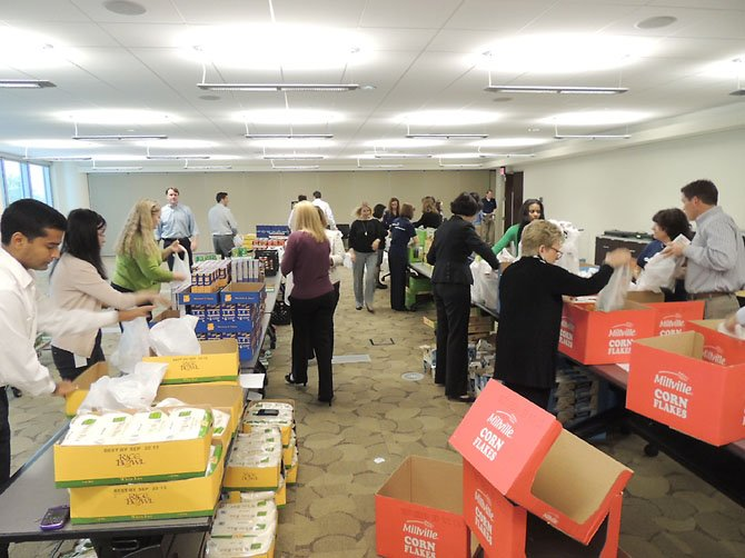 Employees at Capital One assemble food bags to donate to the Lorton Community Action Center (LCAC), a nonprofit organization and food bank based in southeast Fairfax County.