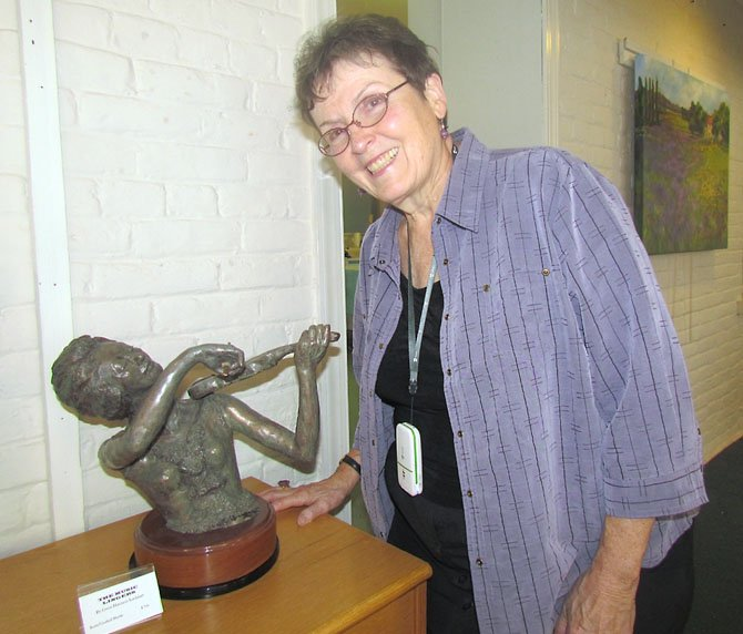 "Gwen Harrison Lockhart pictured with one of her works called ""The Music Lingers."""