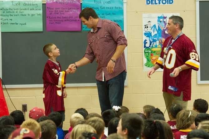 Damian Parson, a sixth grader at Lees Corner Elementary School, won a contest sponsored by talk radio station ESPN980 and the fast food chain Wendy's that brought Redskins Linebacker Ryan Kerrigan, #91, to the school for a visit on Oct. 23.  Kerrigan, who has a math education degree from Perdue University, spoke to students about the importance of staying in school, leading a healthy life, and standing up to bullying. Above, Kerrigan shakes Damian's hand during an assembly as Principal Robert D'Amato looks on.