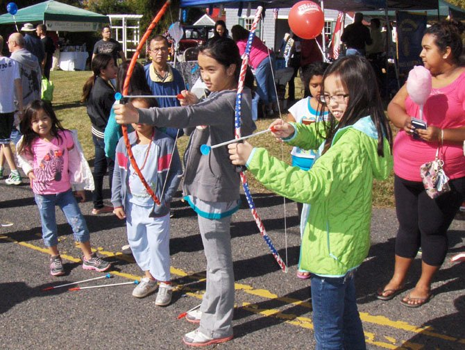 From left: Jennifer Bui and Kaitlin Phan, Colin Powell Elementary sixth-graders, shoot toy arrows at a RulyScapes car.
