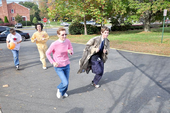 From right, Will Dempsey, 13, Pastor Sandy Kessinger, Michael Petersen, 15, and Christian Markwart, 13, run around the Lutheran Redeemer Church in McLean Saturday, Oct. 27 to raise money for Stop Hunger Now.
