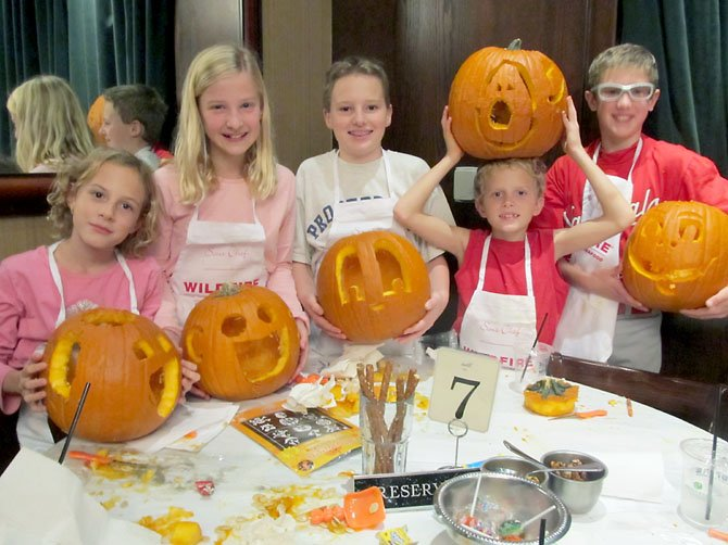 Vienna children donned their chef's aprons and clowned around with their carved pumpkins during Saturday's pumpkin-carving workshop and contest at Wildfire in McLean. (From left) Ashton Cain, 9; Elizabeth Kuhlkin, 9; Ransom Cain, 12, Preston Cain, 9, and Patrick Kuhlkin, 11. A portion of the proceeds from the event benefits Food for Others in Fairfax.
