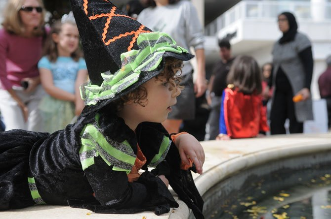 The little witch Sadie Mossop makes a wish after tossing a penny into the pond in the Common.