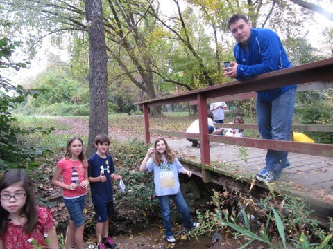 Churchill Road fifth graders in Bob Timke's science class collect water samples in Dead Run Creek. From left are Katherine Dunne, Diana Liddell, Jake Yates, Maggie Snyder and fifth grade teacher Bob Timke.
