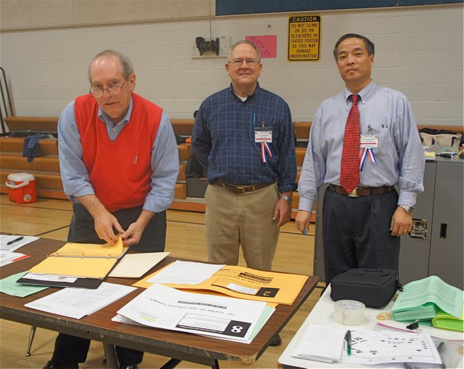 (From left) Precinct 324 election officials have it under control at Herndon Middle School: Dan Linder, Walter Hadlock, and Chief Election Officer Chen Yang.