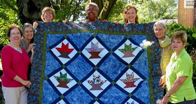 "Quilters hold up their 2012 quilt, ""Baskets of Joy,"" which will be raffled at the MVUC Holiday Shop Saturday, Nov 17."