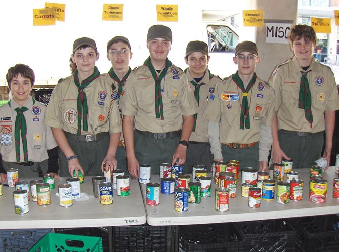 Boy Scouts from Troop 7369 of St. Timothy Catholic School sort canned goods together.