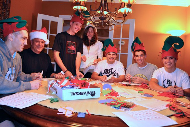 From left: Matt Hagan, Mike Hagan, Drew Magnusson, Kathleen Hagan, Connor Rogers, Kevin Hagan and Reid Lavin attach children's Christmas-gift wishes to ornaments for ONC 2012 giving trees.