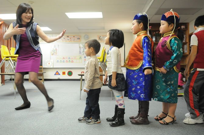 Pre-school rehearse walking together for a presentation on stage during the afternoon concert.