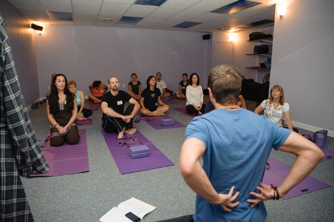 Students prepare to practice yoga at Dream Yoga Studio and Wellness Center in McLean. Experts say confusion and misinformation around yoga can keep some away from the practice.