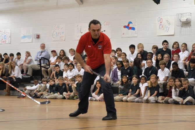 Washington Capitals alumnus Nelson Burton demonstrates a shot during a Washington Capitals Hockey School at Alexandria Country Day School.