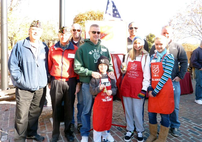 Salvation Army board chairman Walter Clarke (back, second from right), joins volunteers from American Legion Post 24 in Market Square Nov. 17. as part of the annual Red Kettle Campaign. Pictured are: (back) Jim Glassman, Henry Dorton, John Bordner, Jim Lindsay, Clarke and Eric Eide. In front are Mark, Lisa and Caroline Lindsay.