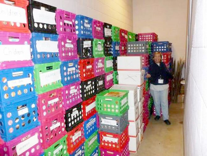 Christine Peterson, president of the Friends of the Richard Byrd Library, displays crates with some of the more than 10,000 book donations the library has received this year for its annual holiday sale.