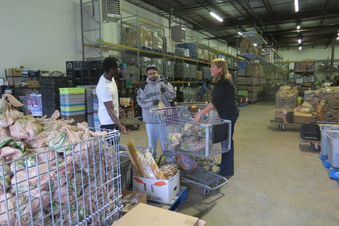 Volunteers help in the Food for Others warehouse on Thursday afternoon.