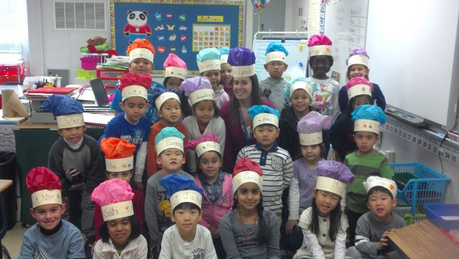 First-grade teacher Caryn Lynch (center) and her students at Colin Powell Elementary wear the chef's hats they made.