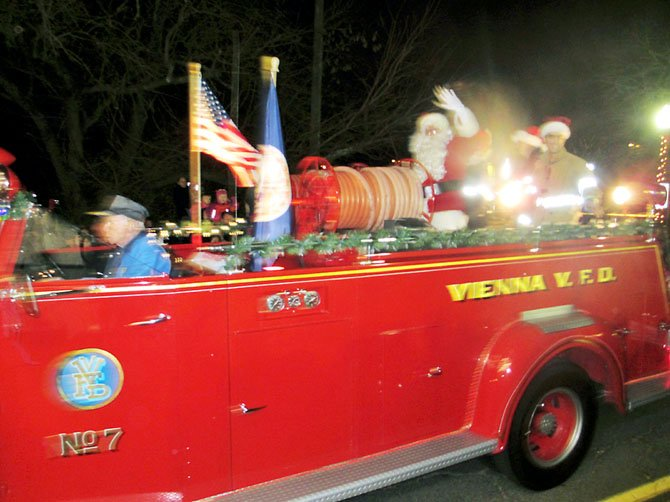 You hear the blaring sirens before the antique fire engine comes into view. Santa Claus arrives in-style to Vienna during the 2012 Church Street Holiday Stroll.
