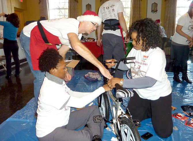 Wheel Nuts Bike Shop owner Ron Taylor, standing, helps volunteers Chariolett Johnson and Linda Powell assemble a bike during the Alexandria Cares Bows, Baskets and Bikes event.