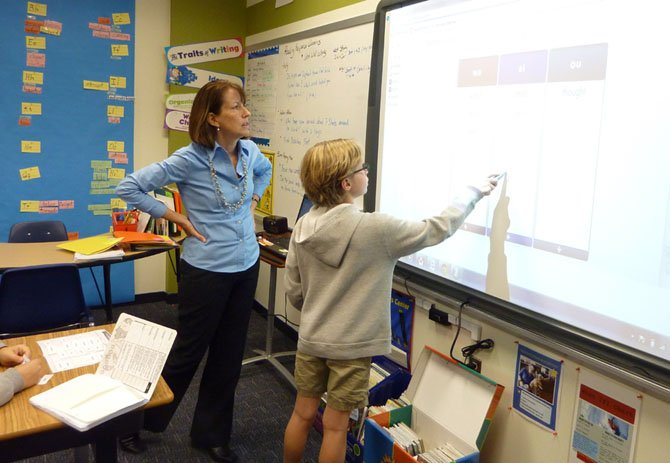 Commonwealth Academy reading and writing specialist Jane Furey works with a student in the new Lower School addition following its dedication Nov. 13.