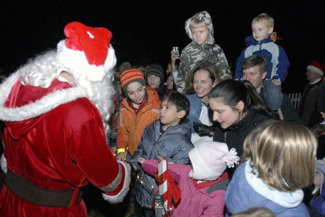 Santa Claus greets children at the Great Falls Tree Lighting ceremony on Sunday evening. The annual event attracts hundreds of area residents and activities including pictures with Santa, Christmas carols, a live Nativity scene and much more.